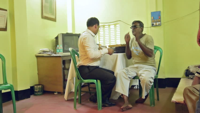 KOLKATA , INDIA - MARCH 19, 2017 : Male Doctor eye specialist checking eye  sight of adult male sitting on a chair, at a free public eye testing camp.