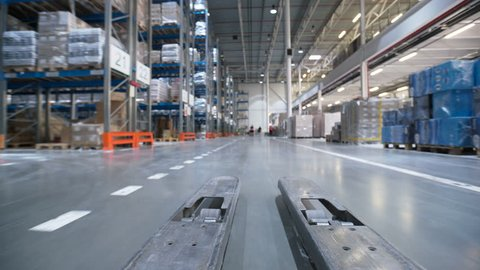 Car trucks move at large rows between shelf with boxes, products, inventories and containers in modern stockroom exterior. People working, sorting and packing. Management of logistics job for export