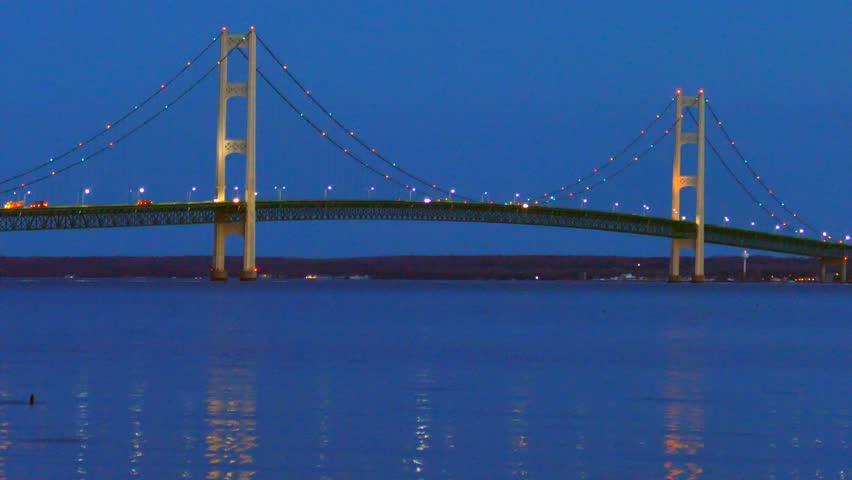 The lights of scenic, Majestic Mackinac Bridge sparkle in deep blue predawn twilight as ducks swim in the foreground, Upper Peninsula of Michigan.
