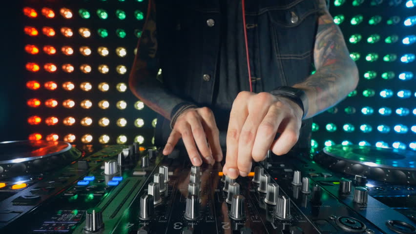 Disco and Club DJ hands mixing at night club party.