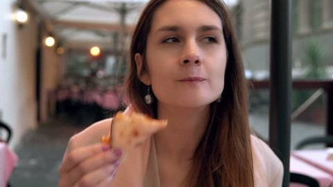 Attractive brunette woman holding slice of pizza and biting it. Hungry girl have a dinner in fast food restaurant.