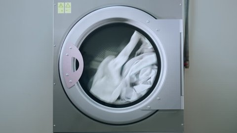 Industrial washing machine washing clothes. Laundry machine working. Industrial machine washing clothing. Laundry washing machine. Industry laundry service