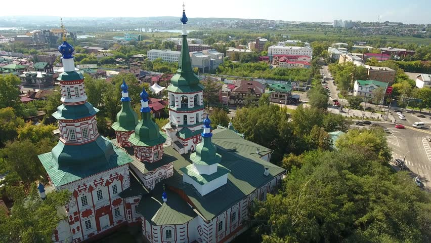 Holy Cross Cathedral Ancient temple. Irkutsk Russia Siberia. Old building View of the city. Sunny summer day blue sky green Park. Unique Aerial view. Drone forward