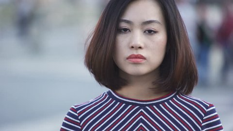 Portrait of chinese serious Woman says No with Finger in the city street