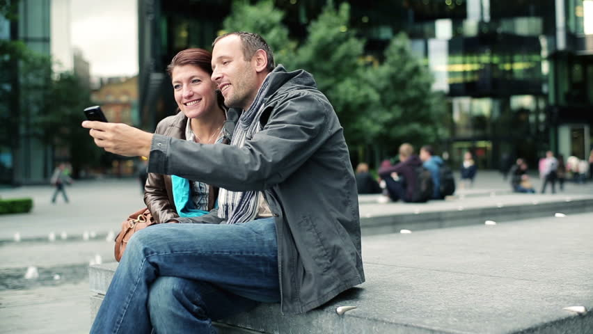 Happy couple taking photo with cellphone in the city