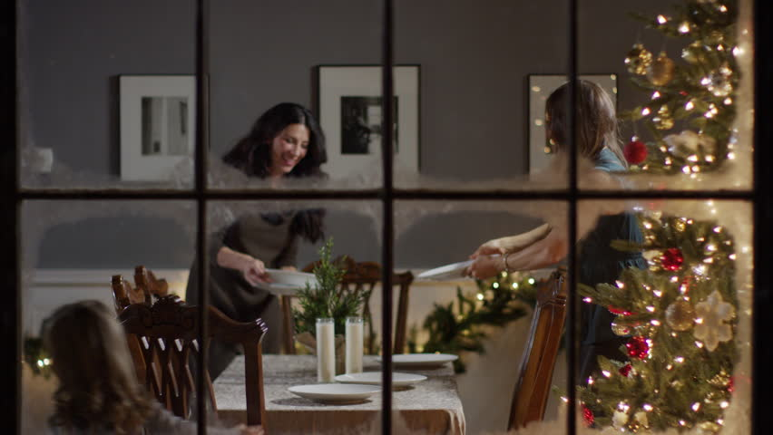 Medium zoom out shot of women setting the table on Christmas / Cedar Hills, Utah, United States