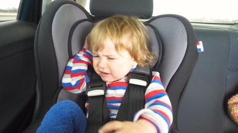 Small child cries and screams in the car. Crying baby boy in car seat. Crying child.