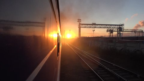Passenger train goes by railway to the orange sun. Sunrise sunset morning. Locomotive From the window FOV, reflection. Populated aerial city at horizon. Dust industry smoke