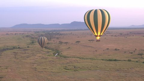 CLOSE UP: Safari hot air balloon flying above vast savannah plains rolling into the distance in stunning Serengeti National Park. Tourists on journey of lifetime in African wildlife wilderness at dawn