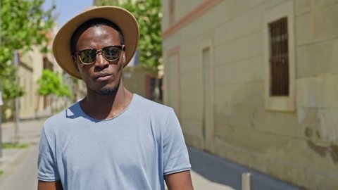 Handsome and trendy young black man walks by the camera while singing and mumbling a catchy tune, with sun shinning on his face.