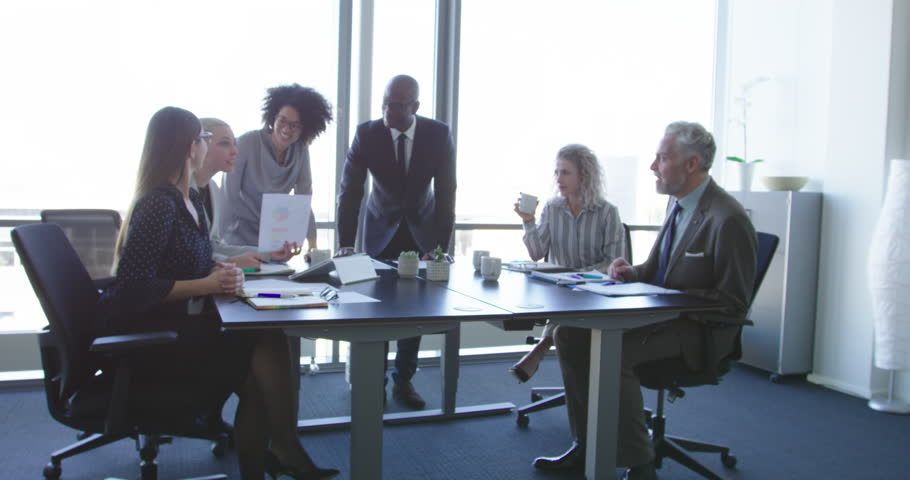Group of diverse business people in formal clothing inside their office discussing or looking at information on a laptop computer | Shutterstock HD Video #26060654