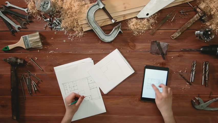 Top view craftsman hands drawing a sketch of floor plan on paper using digital tablet | Shutterstock HD Video #26073371