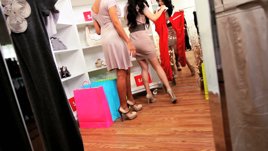African American and Asian Chinese girlfriends shopping together in chic designer boutique