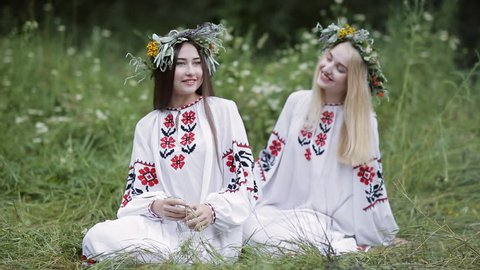 Midsummer. Two girls in Slavic clothes talking while sitting by the fire