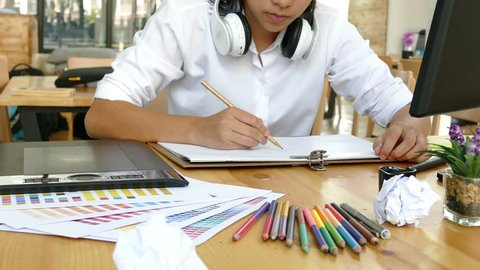 freelance artist graphic designer drawing on white paper with digital tablet and color swatch catalog samples on wood desk - Creativity Editor Ideas Concept