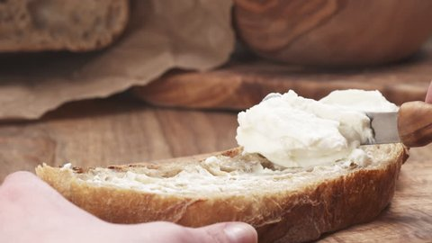 Slow motion of spreading ricotta cheese on fresh rustic bread, 180fps prores footage