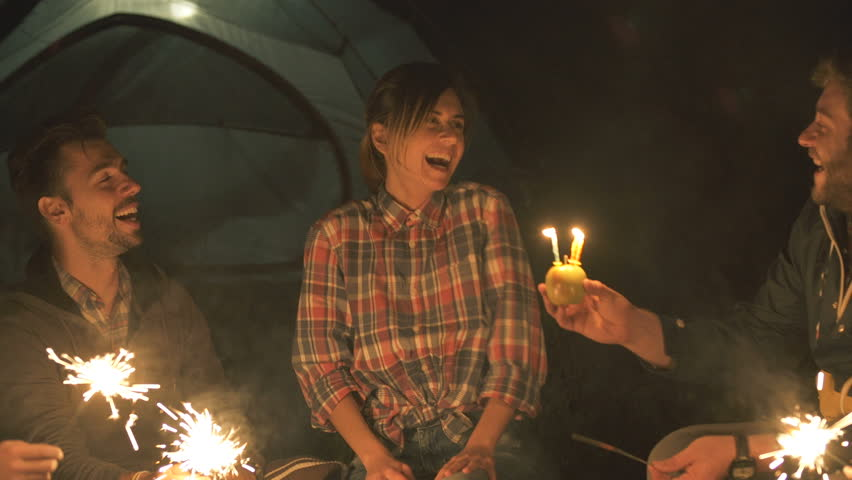 Group of  friends with sparklers having fun around campfire and celebrate birthday