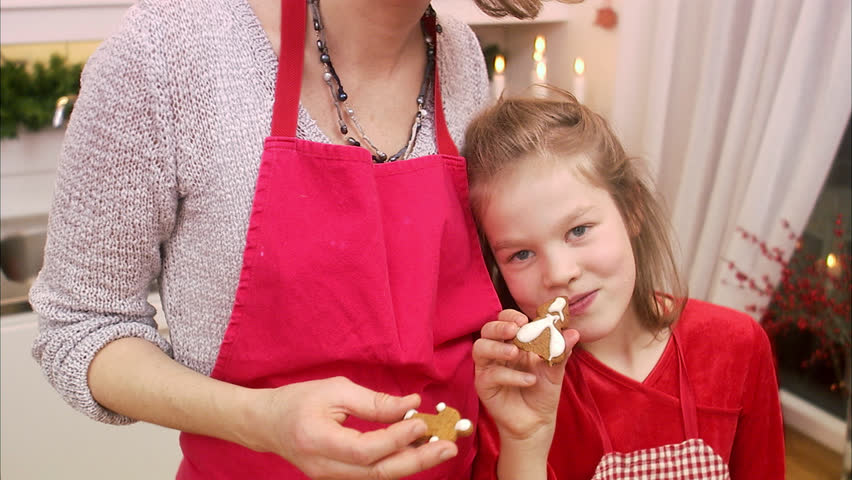 Mother and daughter eating gingerbread biscuits