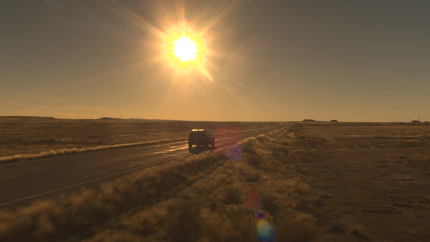 AERIAL: Flying above black SUV car driving on empty highway across beautiful remote wilderness in United States. People on road trip journey traveling across majestic Great Plains in golden light
