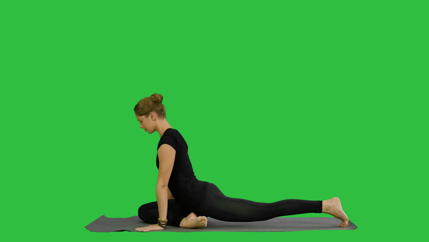 Young beautiful woman doing yoga pose, stretching her body on a Green Screen, Chroma Key