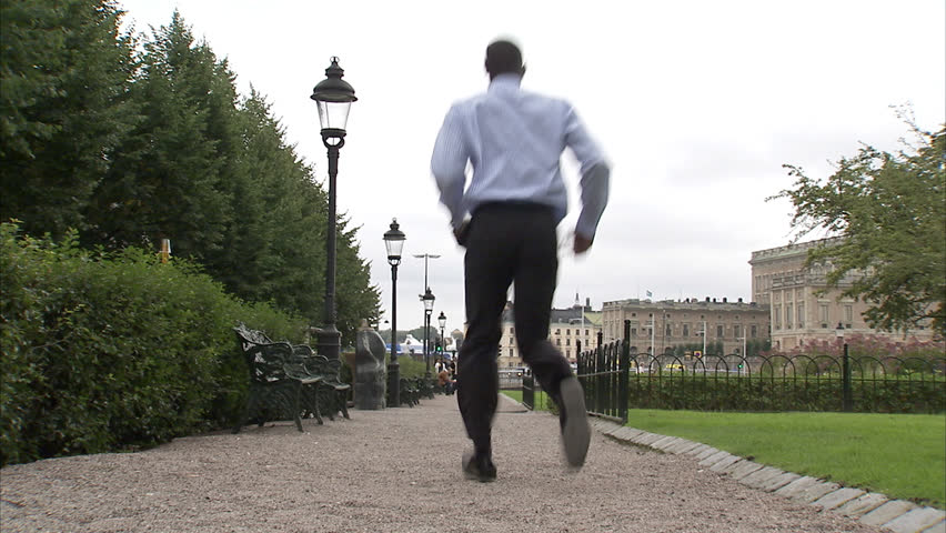 A businessman jumping in a park
