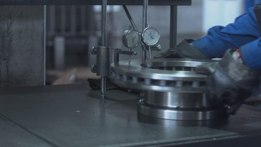 Factory worker inspecting a truck brake disc. 4K UHD