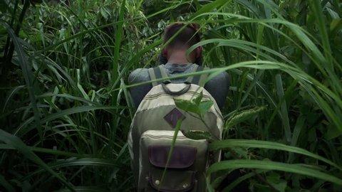 Hikers walking through high shrubbery in the jungle of Peru towards Machu Picchu