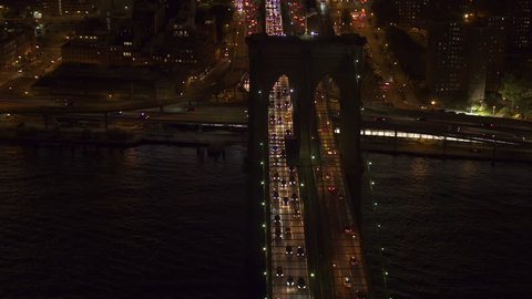 AERIAL HELI SHOT, NO VISIBLE TRADEMARKS Automobile traffic moving across the iconic Brooklyn bridge lit up with lights on magical summer night in New York City. People commuting from work at rush hour