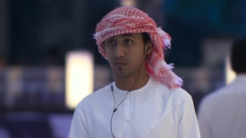 DUBAI, UAE - CIRCA FEBRUARY 2016: A busy modern mall in Arabia despite the effects of the low oil price on the economy, showing a young Arab man wearing traditional Arab dress using his smart phone.