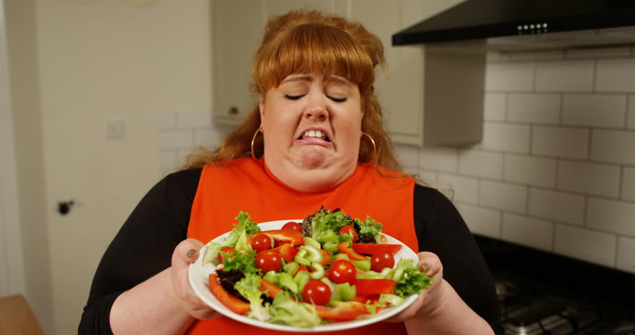 4K Portrait of fun overweight woman feeling sick looking at plate of salad, humorous dieting concept. Slow motion.
