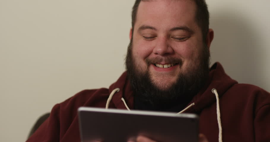 4K Happy overweight man laughing hard at something he sees on computer tablet