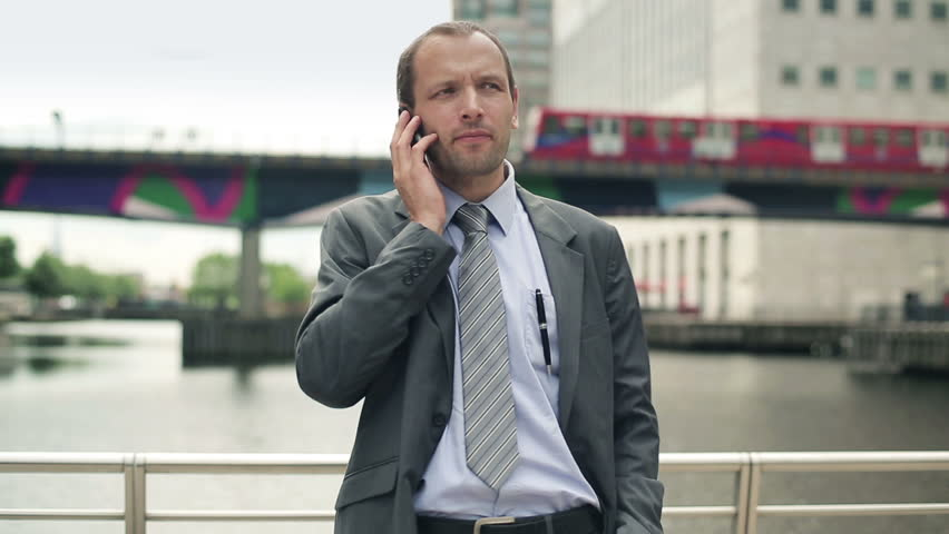 Young handsome businessman talking on mobile phone in the city