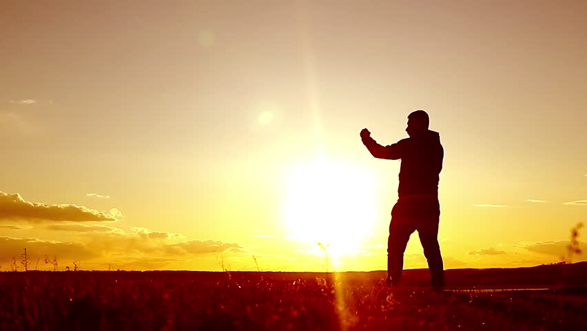 Silhouette of man exercising thai boxing. Silhouette of martial arts man training boxing on the beach over beautiful sunset background. Training karate or boxing on grass field at sunset. | Shutterstock HD Video #26249360