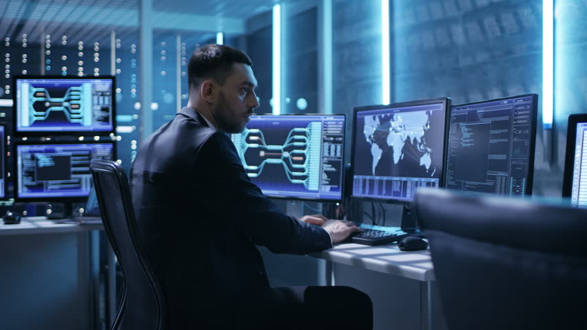 Technical Controller/ Operator Working Between Workstations with Multiple Displays. Possible Power Plant/ Airport Dispatcher/ Government Surveillance/ Shot on RED EPIC-W 8K Helium Cinema Camera.