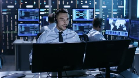 In System Control Center Technical Support Specialist Speaks into Headset while Sitting at His Desk Before Multiple Monitors. His Colleagues are Working in the Background in a Room Full of Displays.