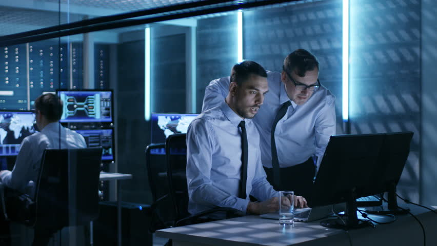 Two Operation Engineers Working on Solving Problems in System Control Room. In the Background Their Colleague, Displays and Server Racks.  Shot on RED EPIC-W 8K Helium Cinema Camera. #26263304
