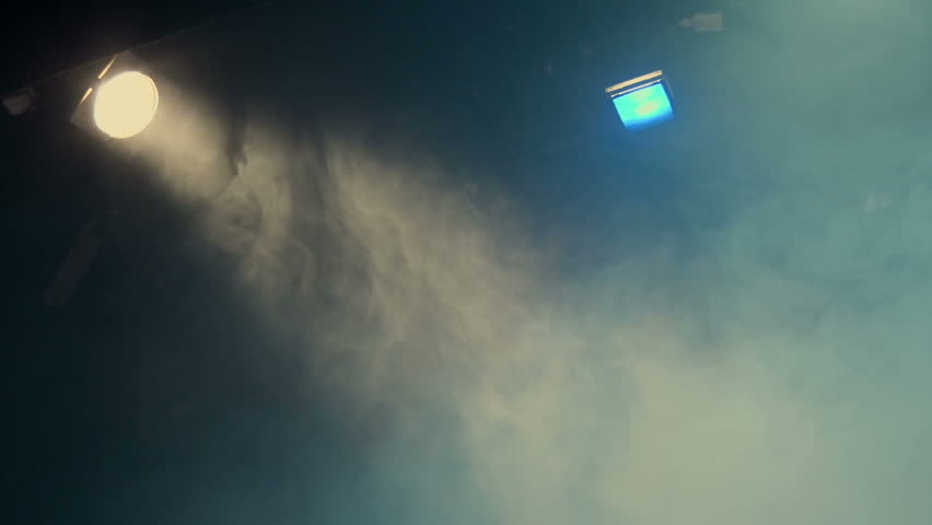 Theatrical smoke. The rays of light from the floodlights at the theater during the performance. Gradual turning off of the light source with dimmer switch. Lighting equipment