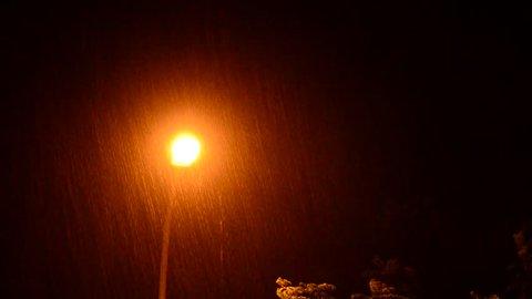 Wind and heavy rain over lamp post night scene.