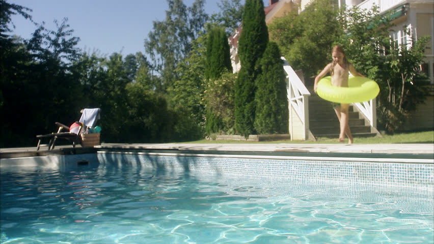 Girl with inflatable ring jumping into swimming pool