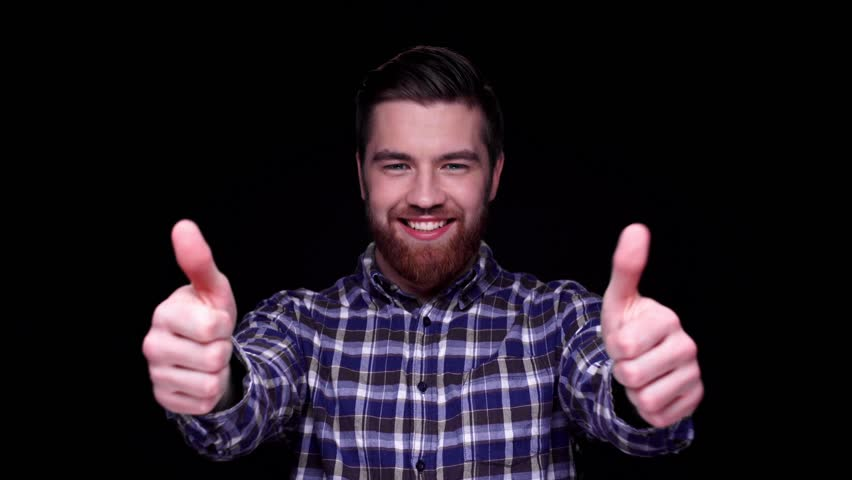 Smiling excited man giving two thumbs up gesture isolated over black background