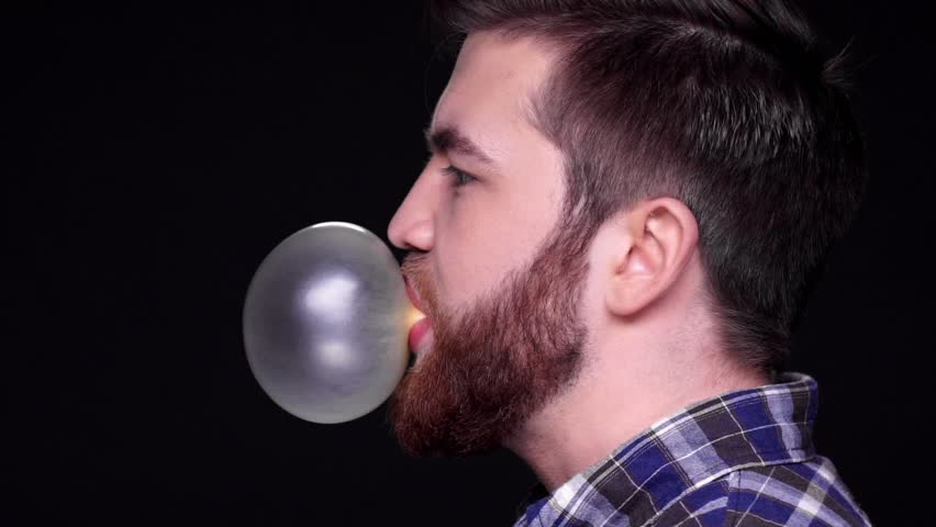 Side view of a young man blowing chewing gum bubble isolated over black