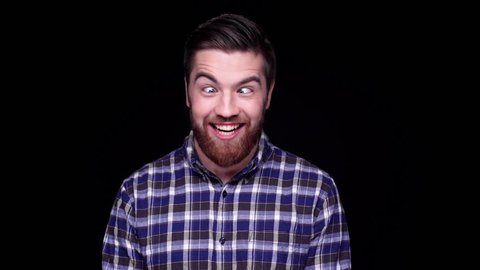 Funny hilarious young man making funny face gestures isolated over black