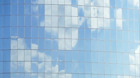 Clouds reflected in windows of modern office building. Background. Close up