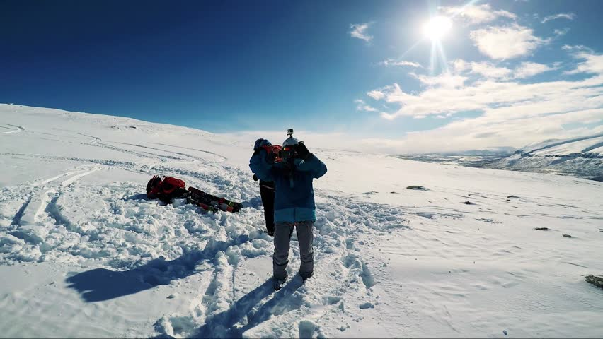 NIKKALUOKTA, SWEDEN - APRIL 22, 2017: Man skier takes a photo his friends on the mountain - sunny day - first person view | Shutterstock HD Video #26303876