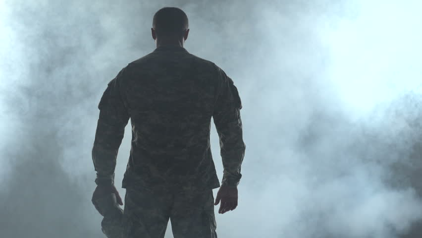Soldier looking down, surrounded by smoke