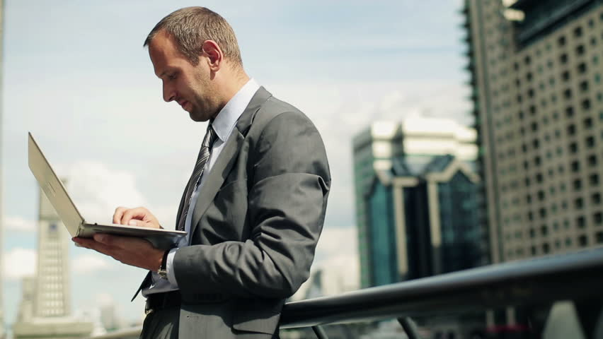 Young handsome businessman working on laptop in the city    Shutterstock HD Video #2633141