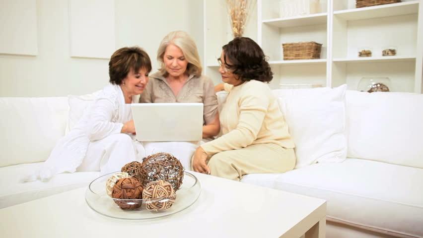 Three senior girlfriends excitement at successful planning using wireless laptop