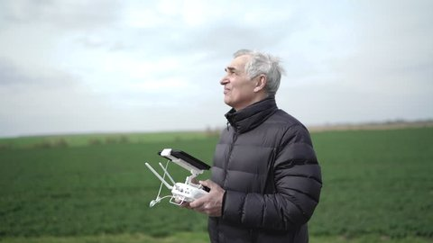 Senior man is getting experience controlling drone at nature. 4K.