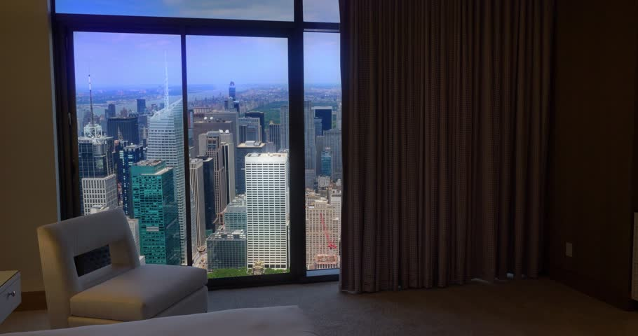 Bedroom curtains automatically open in an upscale New York City apartment to reveal the Manhattan skyline.