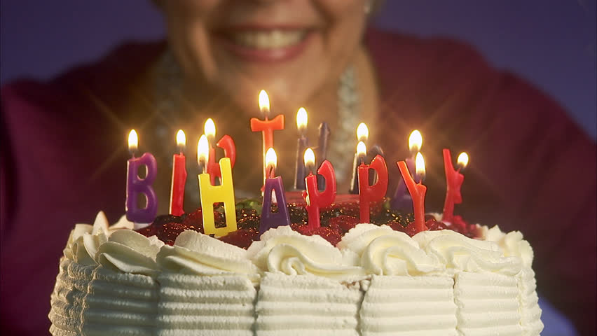 Woman Blowing Out The Candles On A Birthday Cake